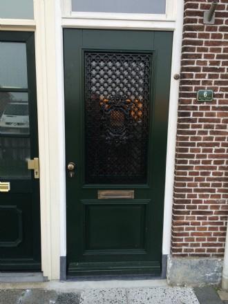 Hard houten voordeur in Harlingen met natuurstenen onderdorpel en neuten